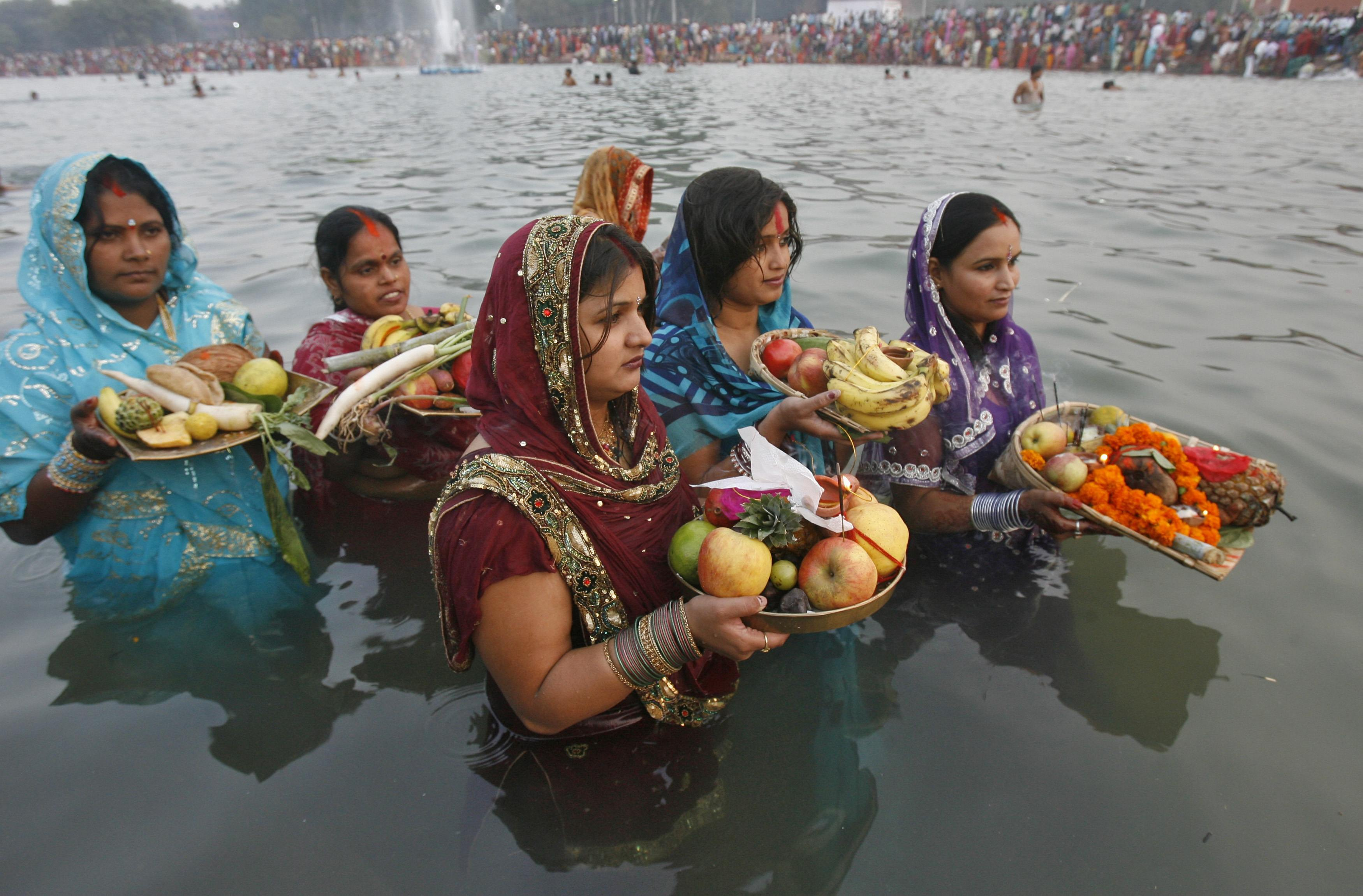 """Hindu devotees offer prayers to the Sun god during the Hindu religious festival """"Chhat Puja"""" in the northern Indian city of Chandigarh November 1, 2011. Hindu devotees worship the Sun god and fast all day for the betterment of their family and society during the festival. REUTERS/Ajay Verma (INDIA - Tags: RELIGION SOCIETY)"""