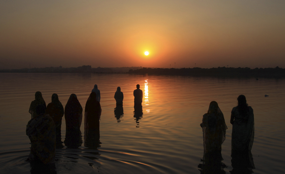 Hindu devotees offer prayers to the sun, during the Chhath Festival at Hussain Sagar Lake in Hyderabad, India, Saturday, Oct. 24, 2009. The Chhath Hindu festival is dedicated to the worship of the sun God. (AP Photo/ Mahesh Kumar A.)