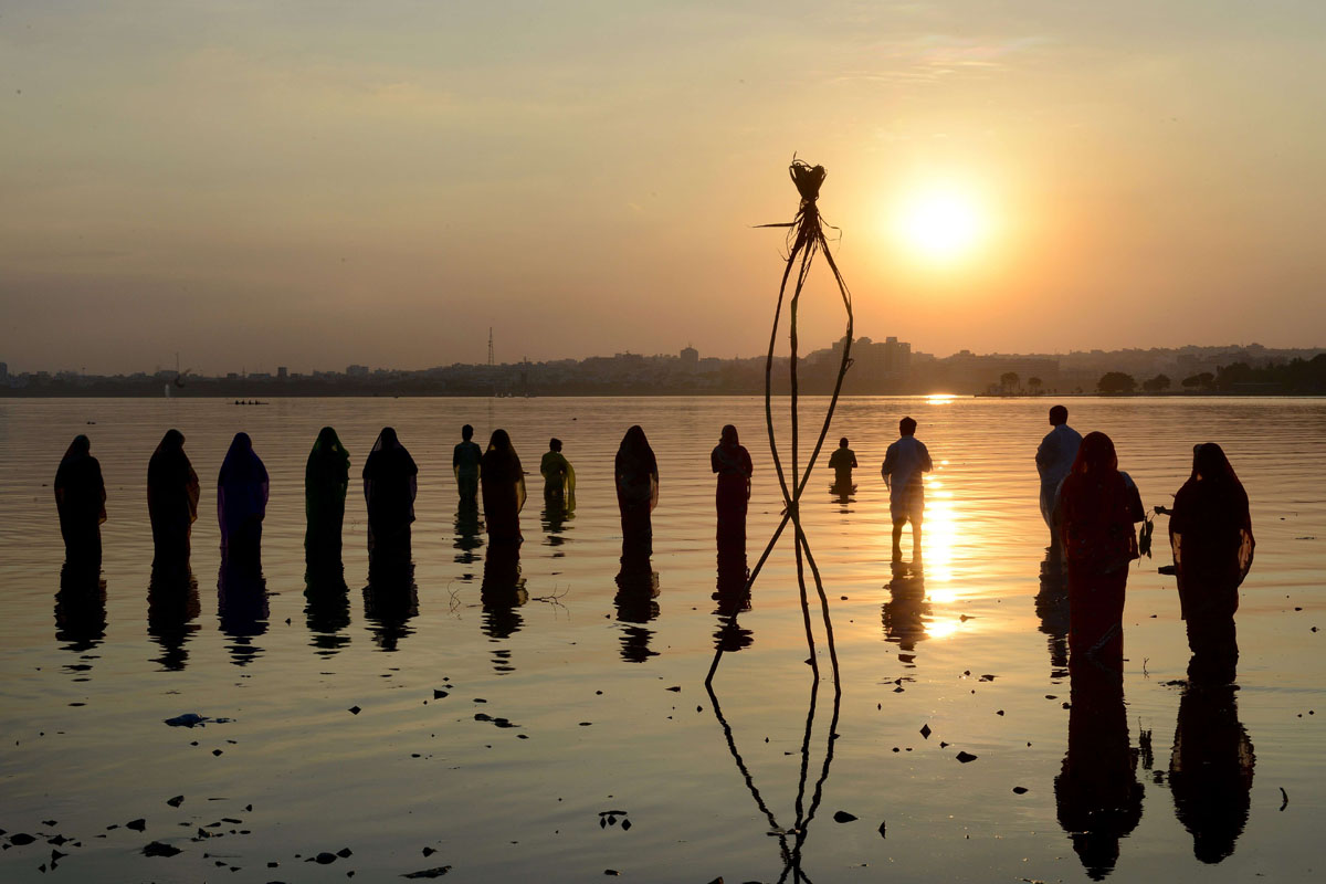 TOPSHOTS Indian Hindu devotees offer prayers to the sun during the Chhath festival on the banks of the Hussain Sagar Lake in Hyderabad on November 17, 2015. Hindu devotees pay obeisance to both the rising and the setting sun in the Chhath festival when people express their thanks and seek the blessings of the forces of nature, mainly the sun and river. AFP PHOTO / NOAH SEELAMNOAH SEELAM/AFP/Getty Images ORG XMIT: