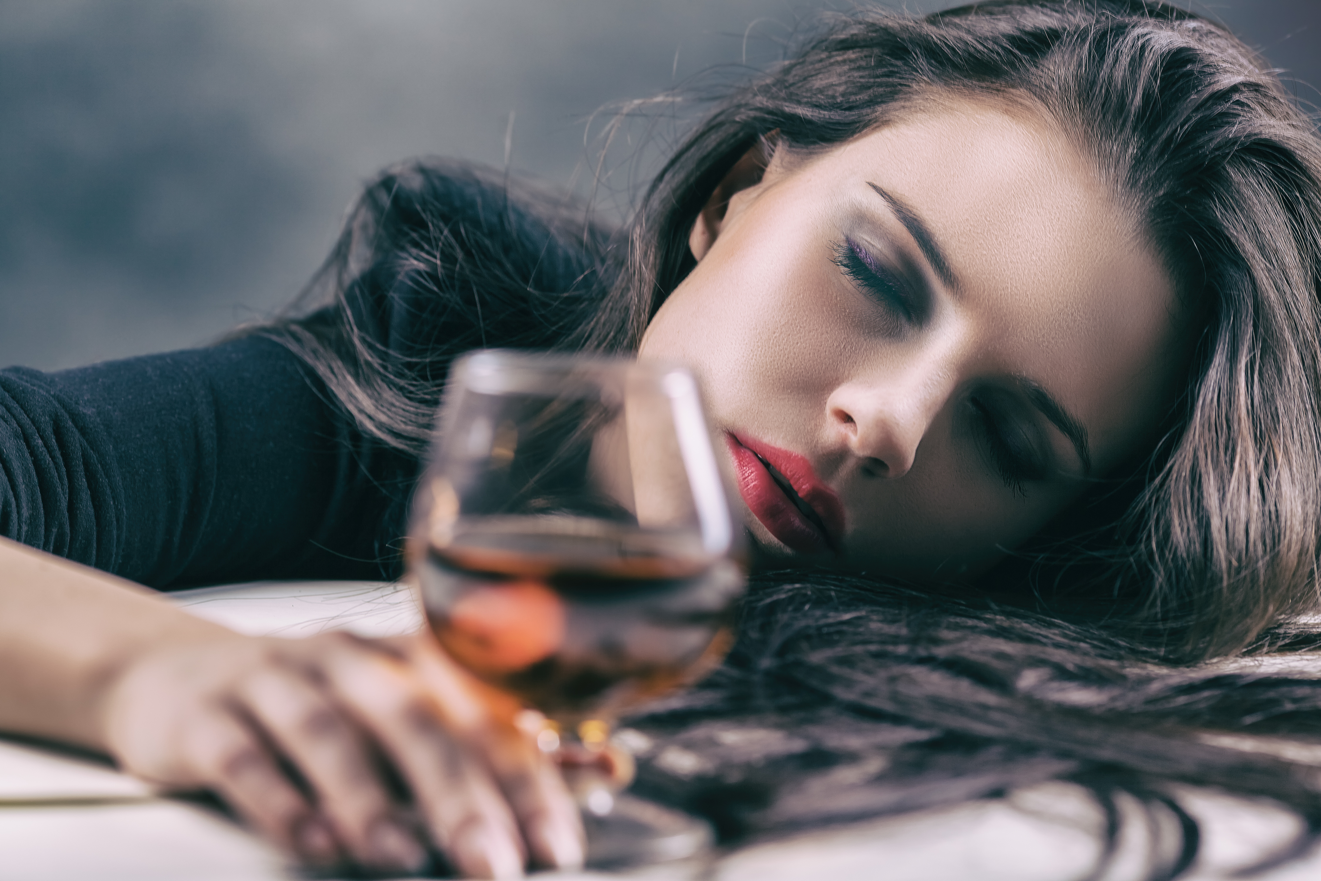 Young beautiful woman drinking alcohol on dark background. Focus on woman