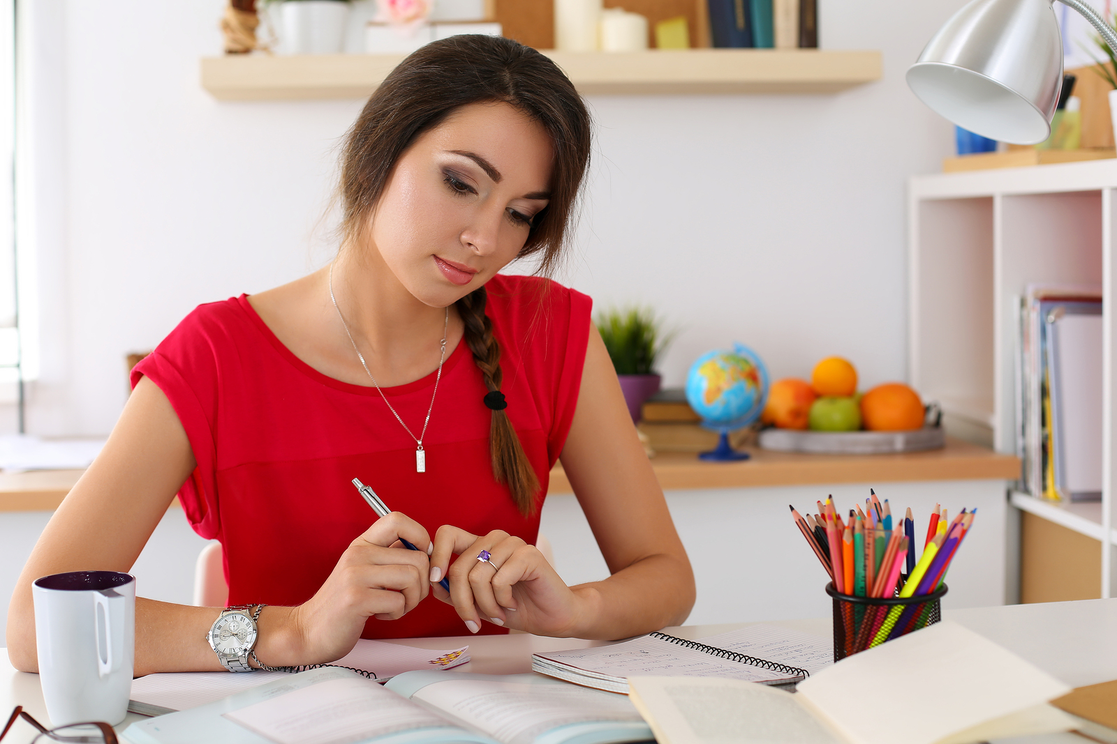 Female student at workplace portrait holding pen and looking in textbooks studying. Woman writing letter list plan making notes doing homework. Education self development and perfection concept
