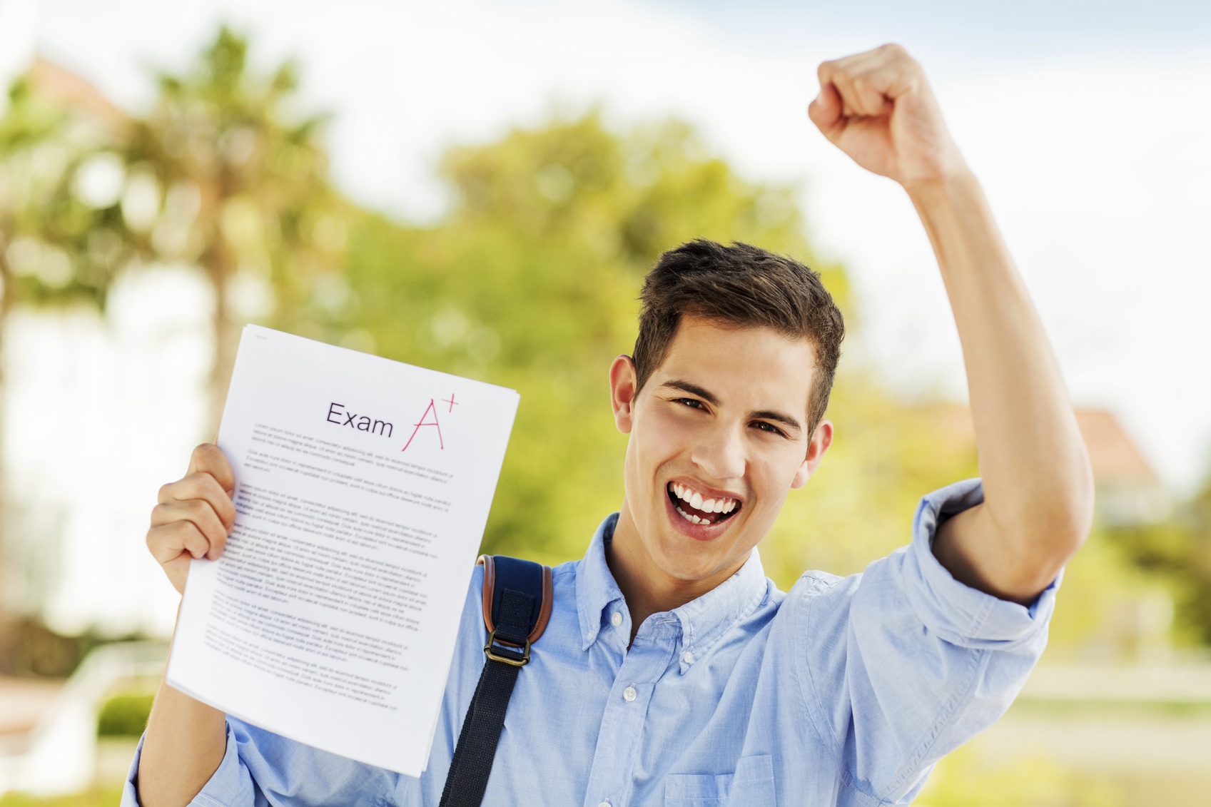 Portrait of happy student clenching fist while holding exam paper with A+ grade on university campus. Horizontal shot.
