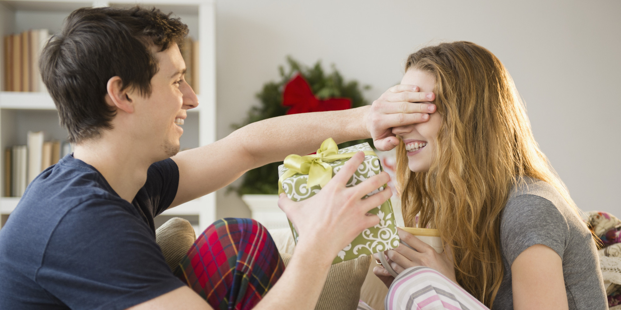 Man surprising girlfriend with gift at Christmas