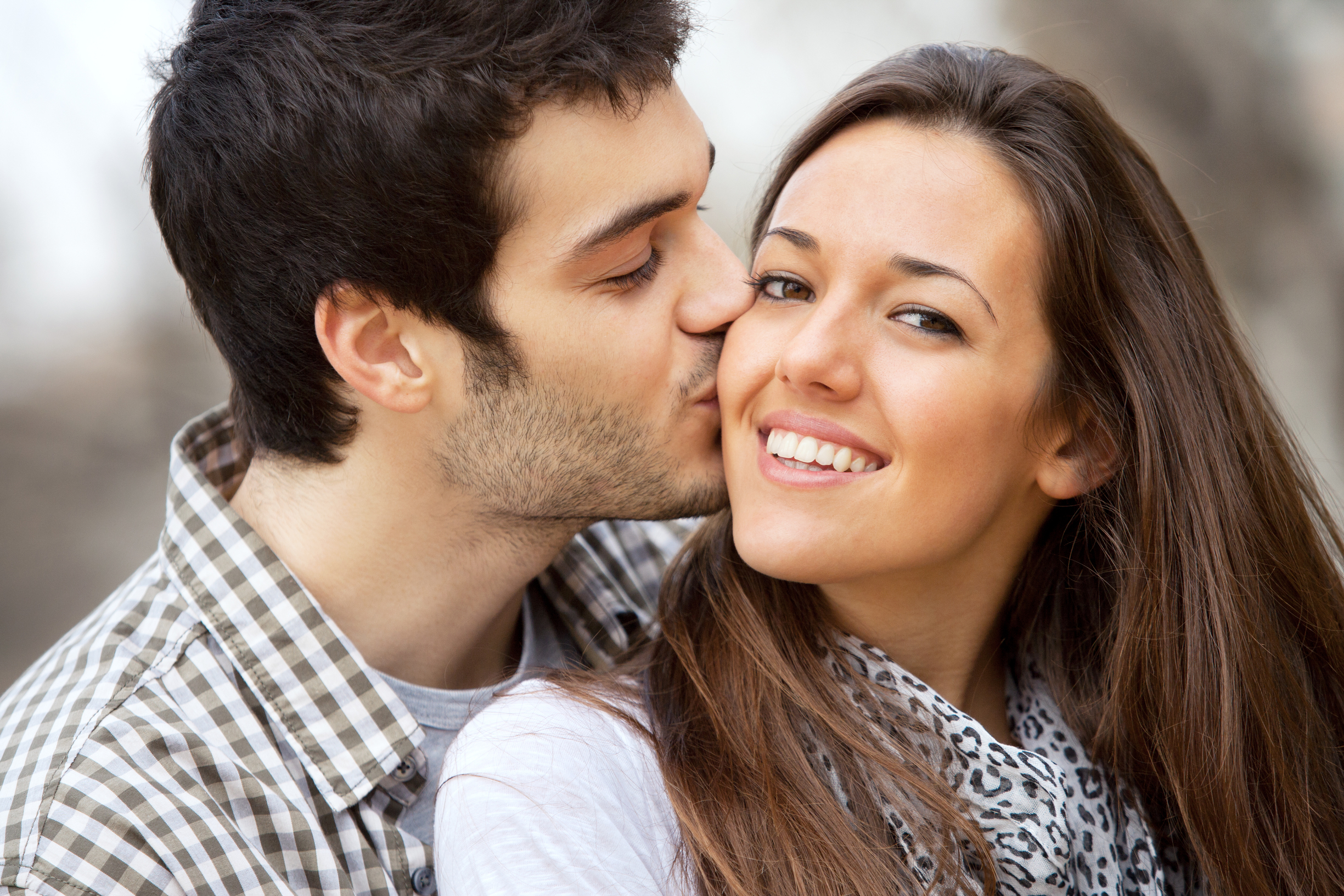 Close up portrait of boy kissing girlfriend on cheek outdoors.