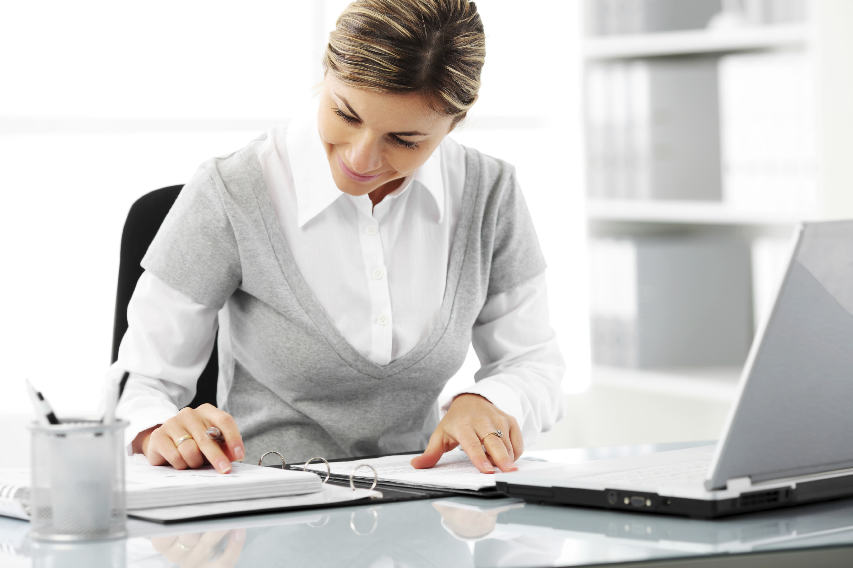 Business woman writing a note at her workplace.