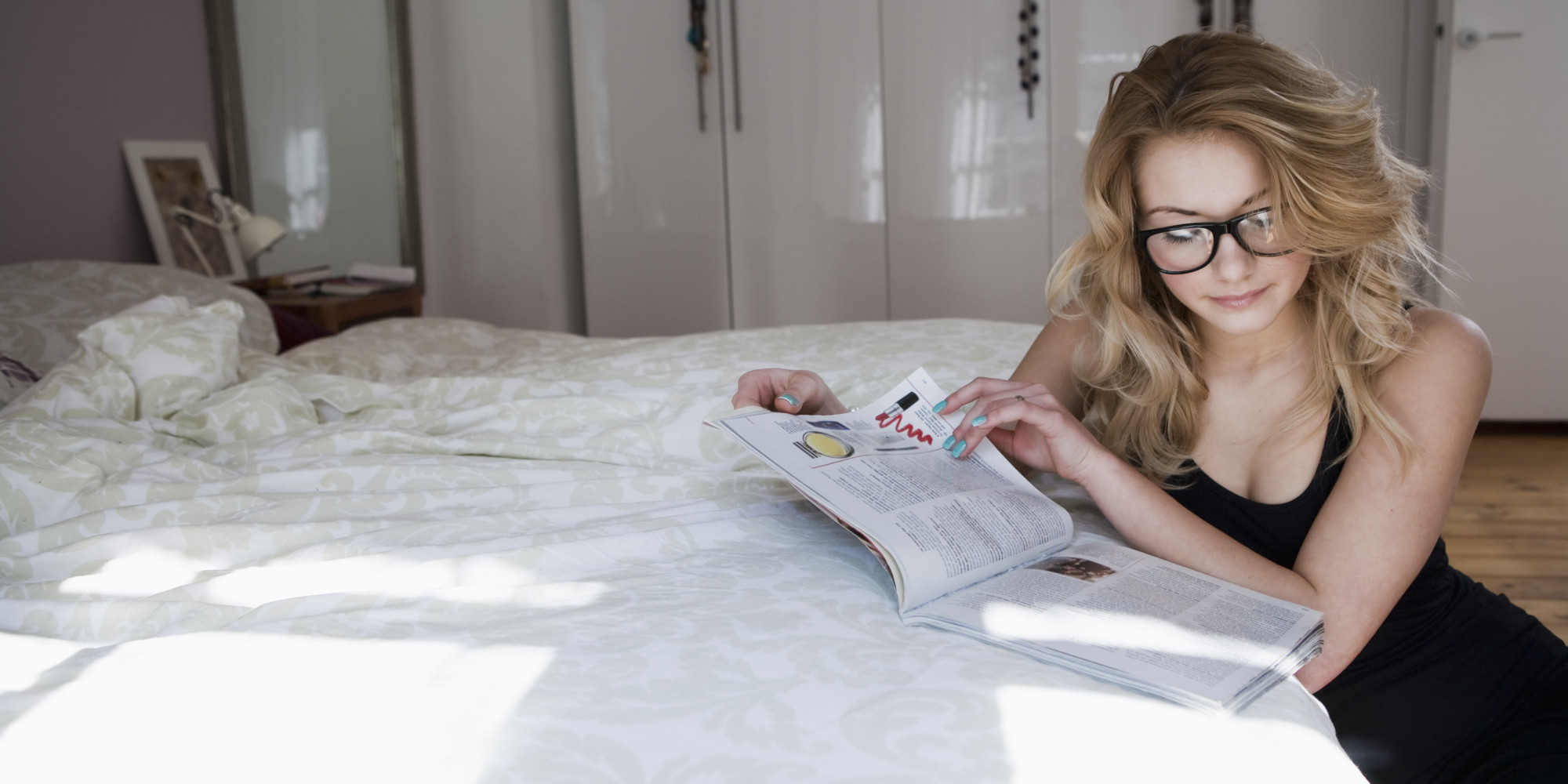 Woman reading a magazine on bed